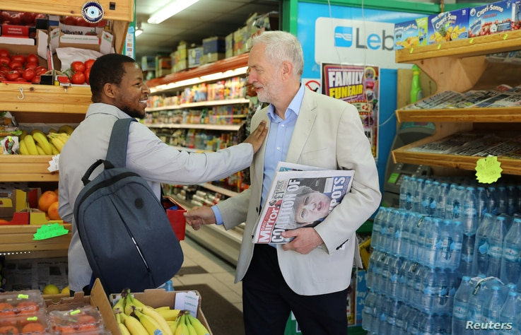 Jeremy Corbyn, leader of Britain's opposition Labour Party, holds newspapers and greets a passer by in Islington, London, Britain June 10, 2017.