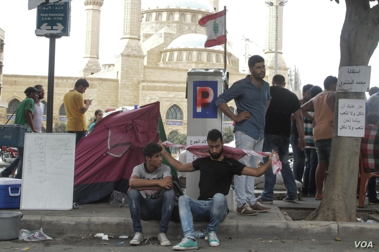 Demonstrators rest near the Ministry of Environment, where protestors have gathered to call for the resignation of Environment minister Mohammad Machnouk, Sept. 16, 2015. (J. Owens/VOA)