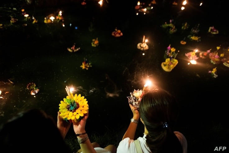 Two women prepare to release 'krathong' on a lake at a park to celebrate Loi Krathong festival in Bangkok on Nov. 22, 2018.