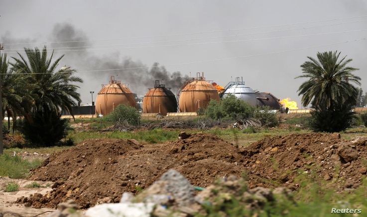 Smoke rises from gas storage tanks after a bomb attack against a state-run cooking gas factory in Taji at Baghdad's northern outskirts, Iraq, May 15, 2016.