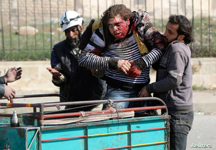 Rescuers help an injured civilian at a site hit by what activists said were barrel bombs dropped by forces loyal to Syria's President Bashar al-Assad in Aleppo's al-Sakhour district, April 2, 2014.