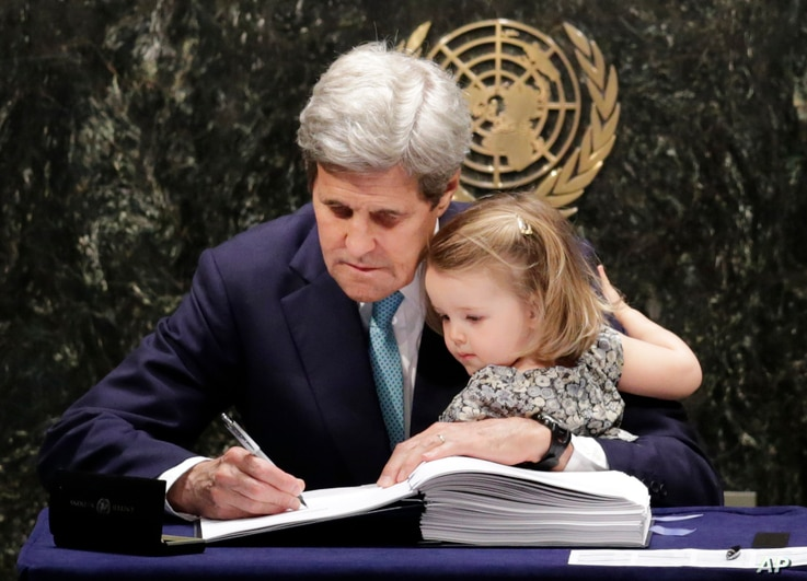 U.S. Secretary of State John Kerry holds his granddaughter Isabel Dobbs-Higginson as he signs the Paris Agreement on climate change, April 22, 2016 at U.N. headquarters.