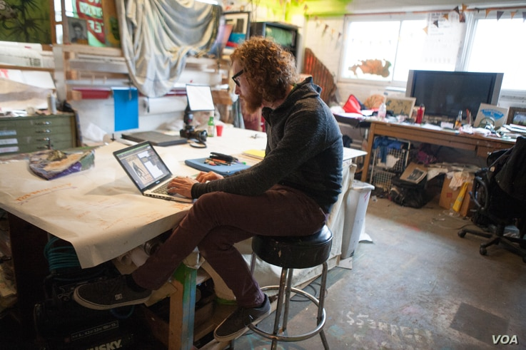 Artist in residence at Union Arts D.C. Graham Boyle is part of Passions and Flags Collective and Art Under Pressure, two artist organizations that have provided pro bono artwork for community social justice campaigns, April 3, 2016. (A. Hernandez/VOA...