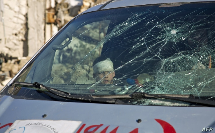 A wounded boy sits inside an ambulance as Syrian rebels and their families gather at the rebel-held al-Amiriyah neighborhood as they wait to be evacuated to the government-controlled area of Ramoussa on the southern outskirts of the city on Dec. 15, ...