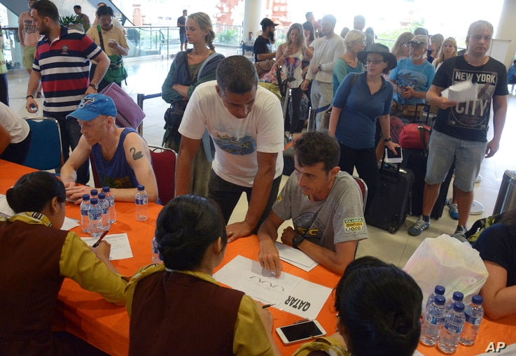 Passengers talk to airline workers as their flights are cancelled at Ngurah Rai International Airport in Denpasar, Bali, Indonesia, Nov. 28, 2017.