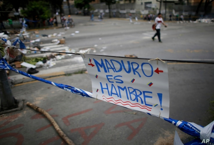 """A sign that reads in Spanish: """"Maduro is hunger!"""" forms part of a barricade made by demonstrators during a 48-hour general strike beginning July 26, 2017. In the capital, Caracas, many residents stayed home in observance of the strike."""