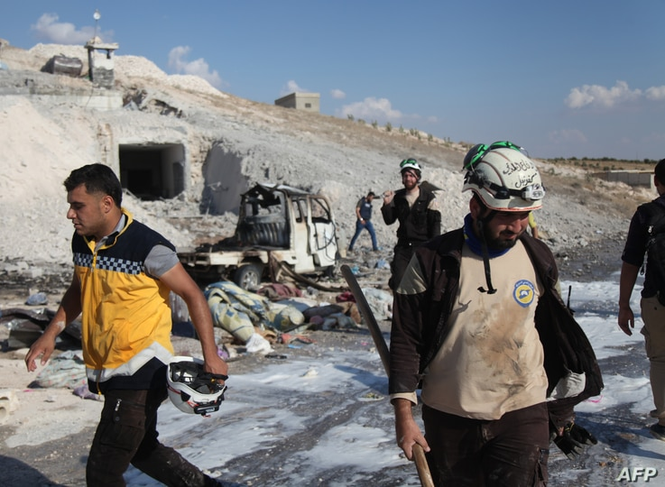 Syrian civil defense members search near a burned vehicle and personal belongings at a site in Hass town after an airstrike in the southern part of Syria's Idlib province, Sept. 8, 2018.