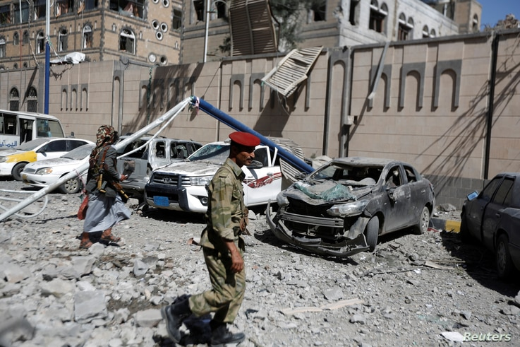 Houthi militants walk past damaged cars outside the Presidential Compound after it was hit by air strikes in Sanaa, Yemen, May 7, 2018.