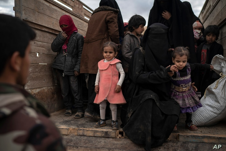 Women and children exit the back of a truck to be screened by U.S.-backed Syrian Democratic Forces after being evacuated out of the last territory held by Islamic State militants, in the desert outside Baghuz, Syria, Feb. 27, 2019.