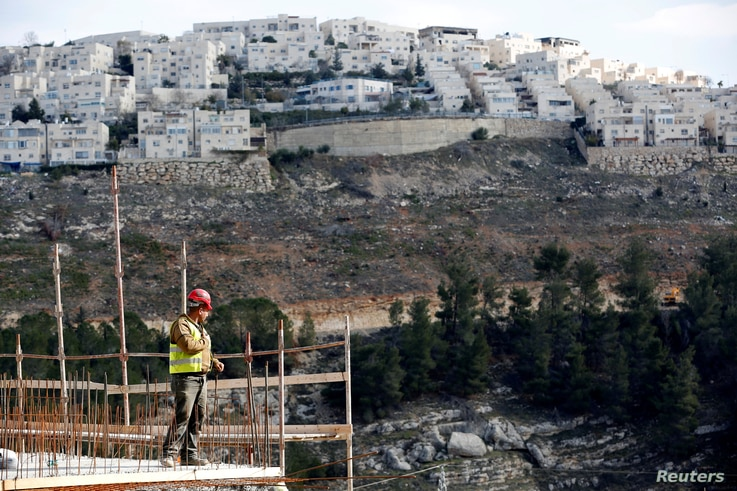 A laborer works at a construction site in the Israeli settlement of Ramot, as the Israeli settlement of Ramat Shlomo is seen in the background, in an area of the occupied West Bank that Israel annexed to Jerusalem, Jan.  22, 2017.