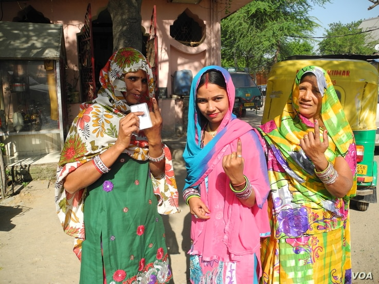 Residents of a low income settlement in Gurgaon, adjoining New Delhi, hold up their fingers after voting, April 10, 2014. (Anjana Pasricha/VOA)