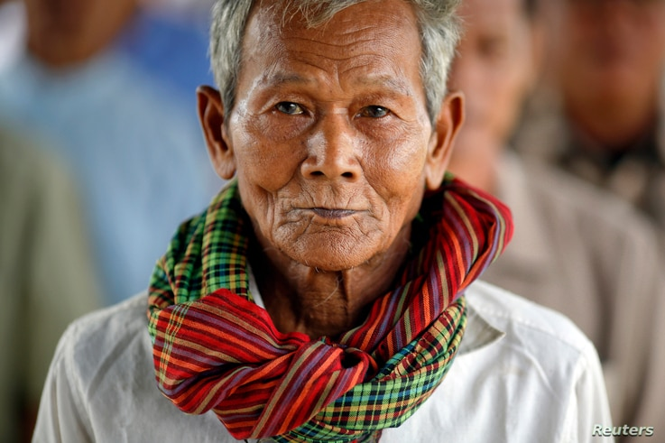 FILE - Sok Teng, 73, waits with other survivors and relatives of victims of the Khmer Rouge regime to enter the Extraordinary Chambers in the Courts of Cambodia (ECCC) to attend the delivery of verdict in the trial of former Khmer Rouge head of state...