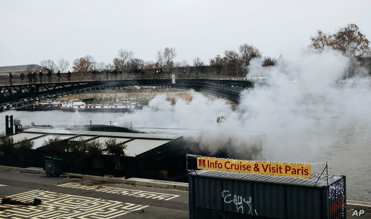 Tear gas is thrown along the Seine river banks during a protest in Paris, Jan. 5, 2019. Hundreds of protesters were trying to breathe new life into France's apparently waning yellow vest movement with marches in Paris and gatherings in other cities. ...