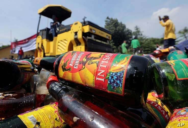 Government officials destroy bottles of illegal alcohol confiscated in Serpong, on the outskirts of Jakarta, Indonesia, April 13, 2018.