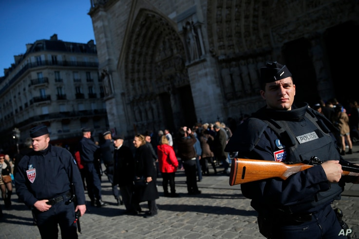 Police officers patrols in front of Notre Dame cathedral following Friday's attacks on Paris, Nov. 15, 2015. Thousands of French troops deployed around Paris on Sunday and tourist sites stood shuttered.