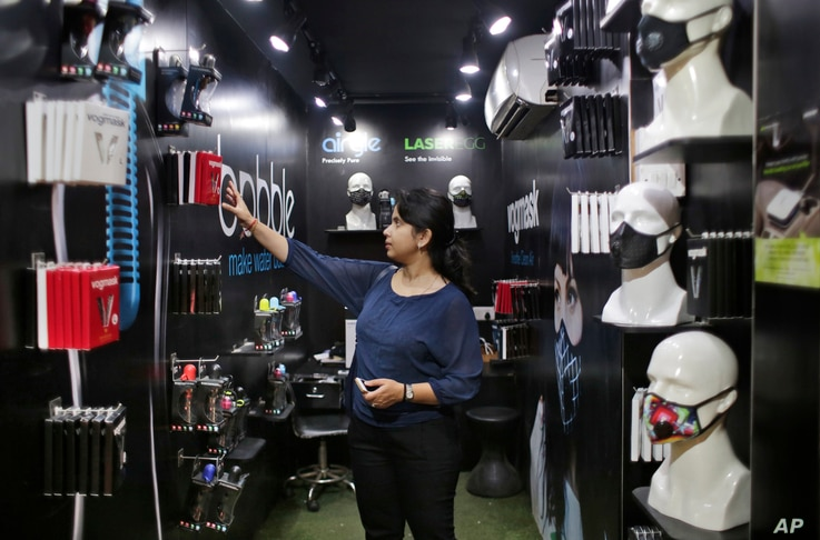 An Indian woman looks for air pollution mask inside a shop in New Delhi, India, Nov. 4, 2016. A new report from UNICEF says about a third of the 2 billion children in the world who are breathing toxic air live in northern India and neighboring countr...
