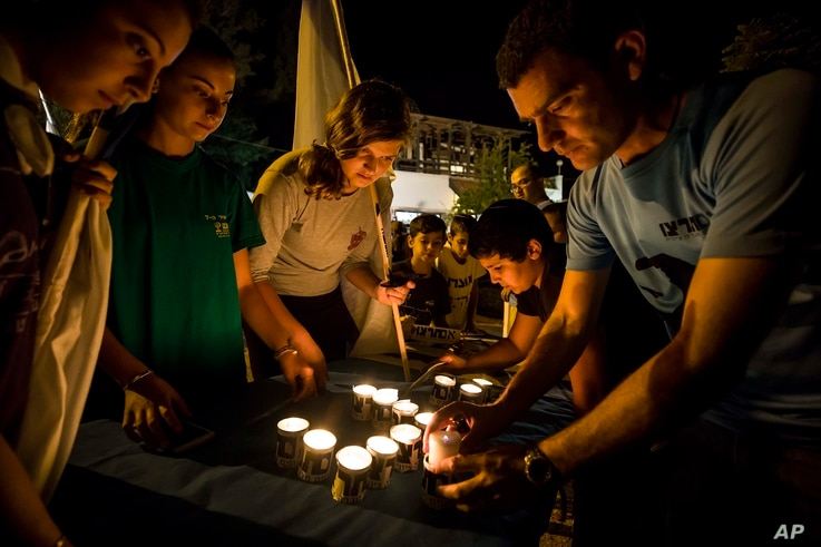 Israelis light candles in the Israeli settlement of Halamish, July 22, 2017. Israel's military has sent more troops to the West Bank and placed forces on high alert a day after a Palestinian stabbed to death three members of an Israeli family and Isr...