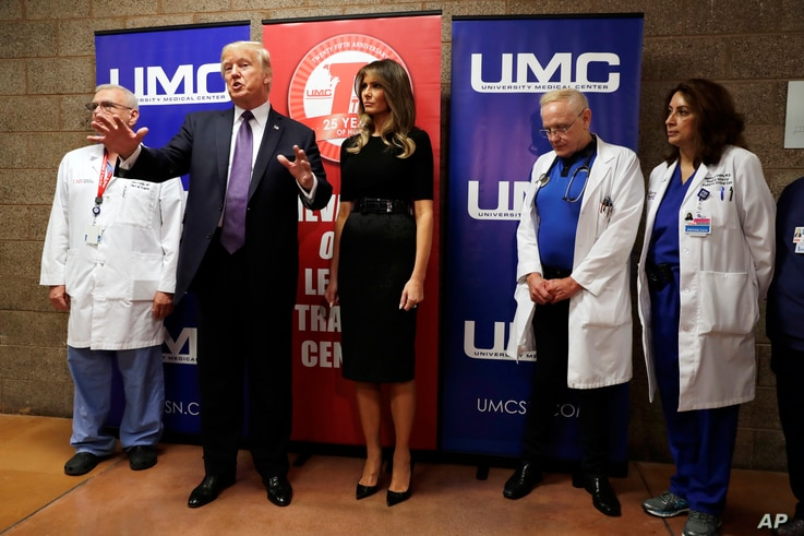 President Donald Trump talks as first lady Melania Trump and surgeon Dr. John Fildes, left, listens at the University Medical Center after Trump met with survivors of the mass shooting, Oct. 4, 2017, in Las Vegas.