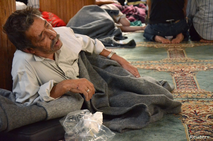 A survivor from what activists say is a gas attack rests inside a mosque in the Duma neighbourhood of Damascus August 21, 2013.