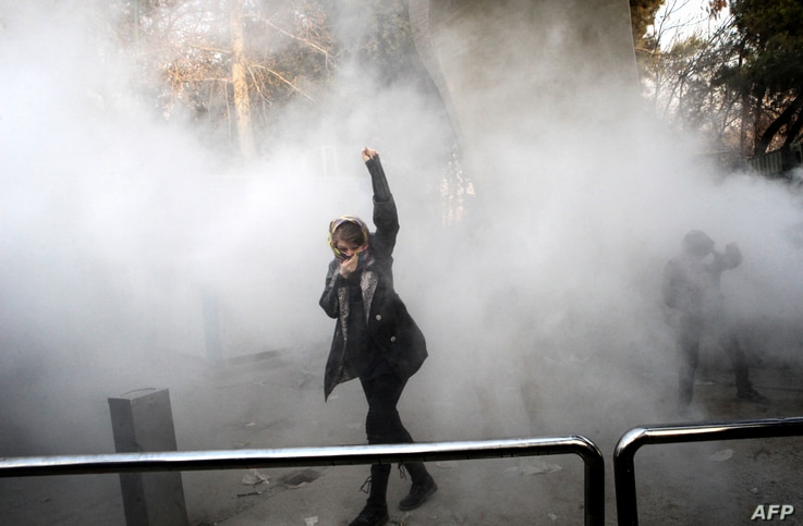 An Iranian woman raises her fist amid the smoke of tear gas at the University of Tehran during a protest, in Tehran, Iran, Dec. 30, 2017.