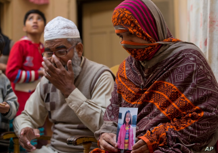 Nusrat holds a photo of her daughter, Zainab Ansari, who was raped and killed, as her husband, Mohammed Amin in Kasur, sits beside her in Kasur, Pakistan, Jan. 18, 2018.