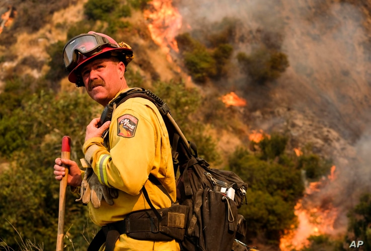 FILE - A crew member with California Department of Forestry and Fire Protection battles a brushfire on the hillside in Burbank, Calif., Sept. 2, 2017.