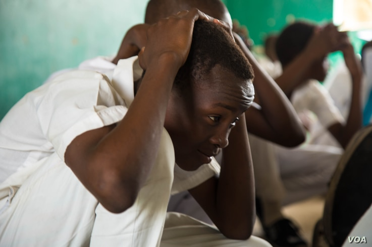 A high school student ducks in a classroom during a safety drill. Students in Maiduguri have begun participating in drills so they will know how to respond in the event of a Boko Haram attack.