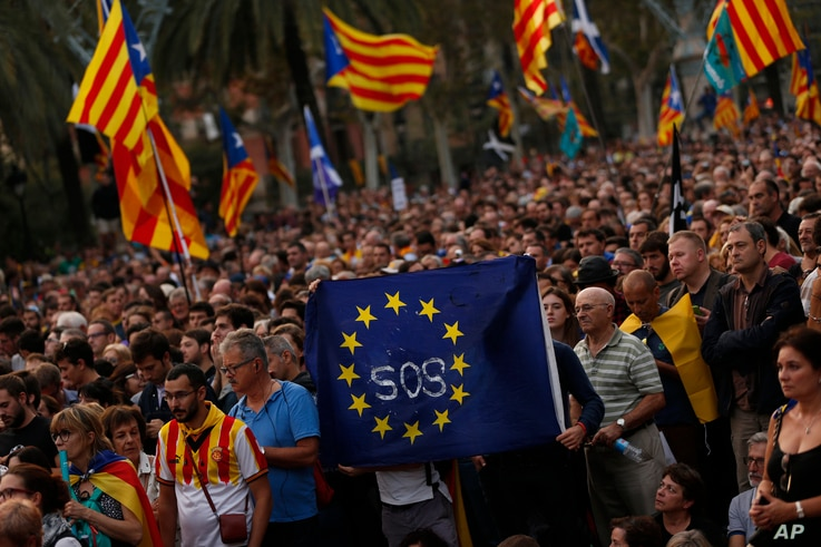 Pro-independence supporters hold a European Union flag during a rally in Barcelona, Spain, Oct. 10, 2017. Catalan President Carles Puigdemont said during his speech in the parliament that the region remained committed to independence but said it shou...