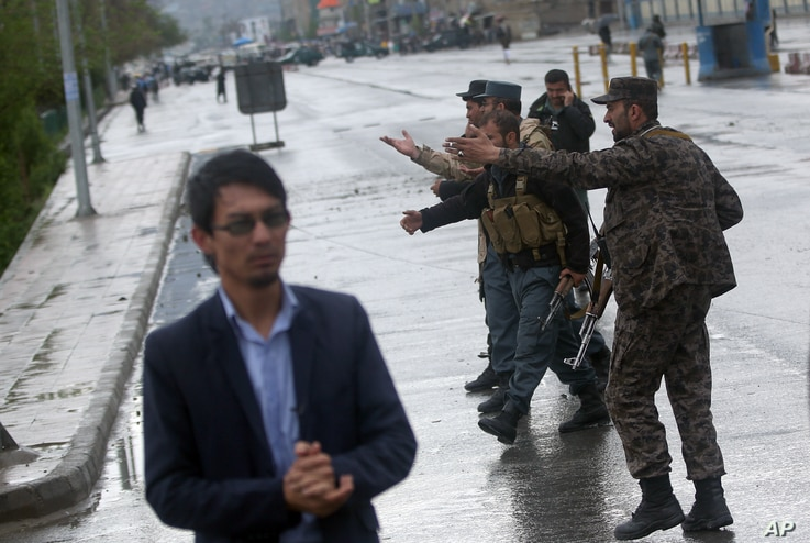 FILE - Afghan security forces shout at journalists at the site of a deadly Taliban-claimed suicide attack in Kabul, Afghanistan, April 19, 2016.