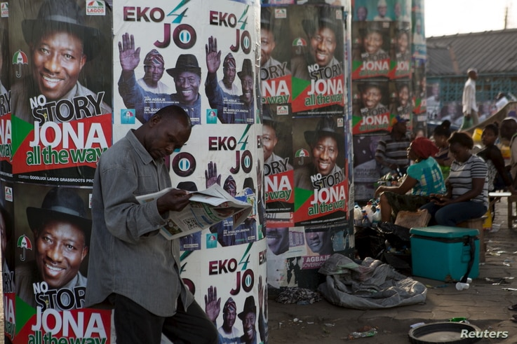 A man reads a newspaper in front of electoral campaign posters in Lagos, Nigeria, March 30, 2015.
