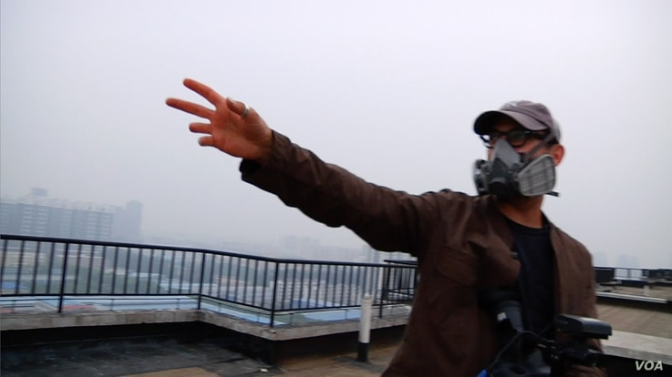 Josh Fox gestures to the oppressive smog from a rooftop in Beijing. (Credit: International WOW Company)
