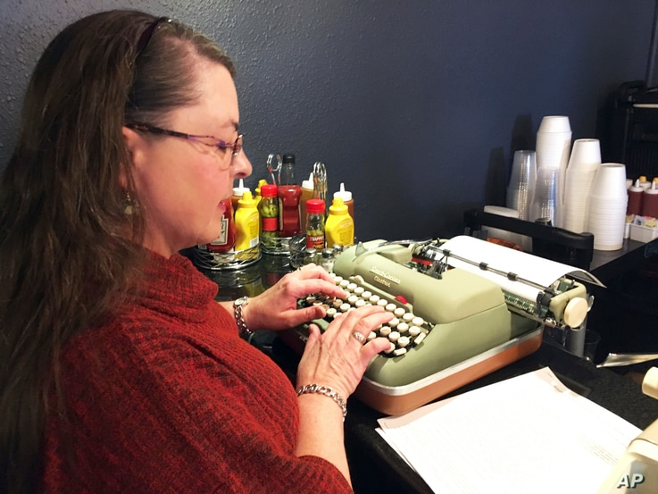 "Andrea Kittle of Albuquerque, N.M., tries out a vintage Smith Corona electric typewriter at a ""type-in"" in Albuquerque, April 23, 2017."
