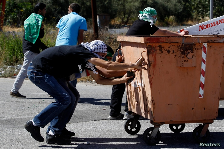 Palestinian protesters take cover during clashes with Israeli troops at a demonstration against the Israeli offensive in Gaza, near the Israeli settlement of Bet El, near Ramallah July 25, 2014. U.S. Secretary of State John Kerry pressed regional lea...