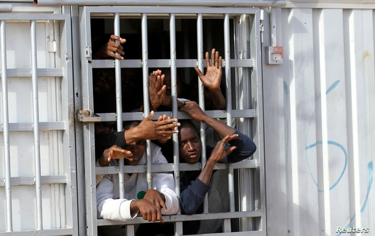 FILE -  Illegal migrants, who have been detained after trying to get to Europe, look out of barred door of a detention hut at a detention camp in Gheryan, outside Tripoli, Libya.