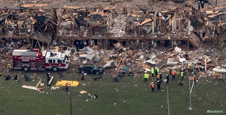 Police and rescue workers stand near a building which was left destroyed from a massive explosion at a nearby fertilizer plant in the town of West, near Waco, Texas April 18, 2013.