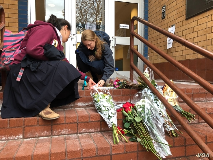 Two young girls light candles at a memorial on Oct. 29, 2018, in front of the Jewish Community Center of Greater Pittsburgh, one of the sites chosen for the first day of funerals.