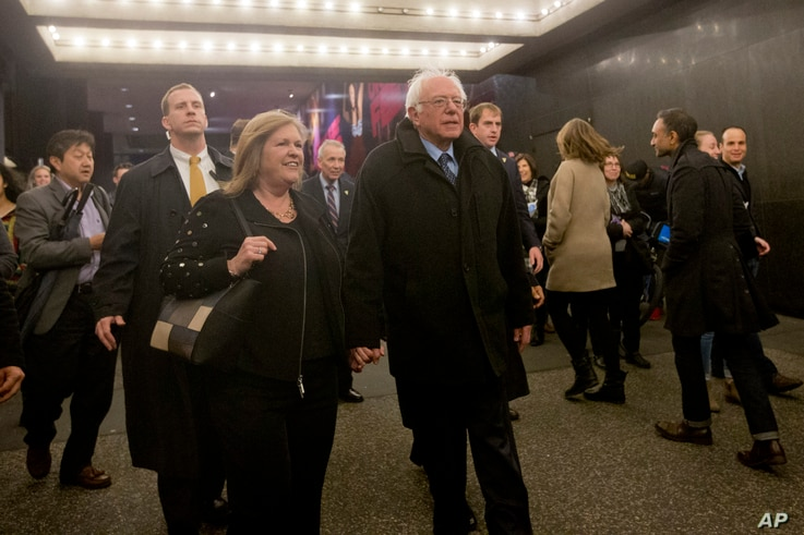 """Democratic presidential candidate Bernie Sanders and his wife, Jane, walk in Times Square on their way to see the Broadway show """"Hamilton"""" in New York, April 8, 2016."""