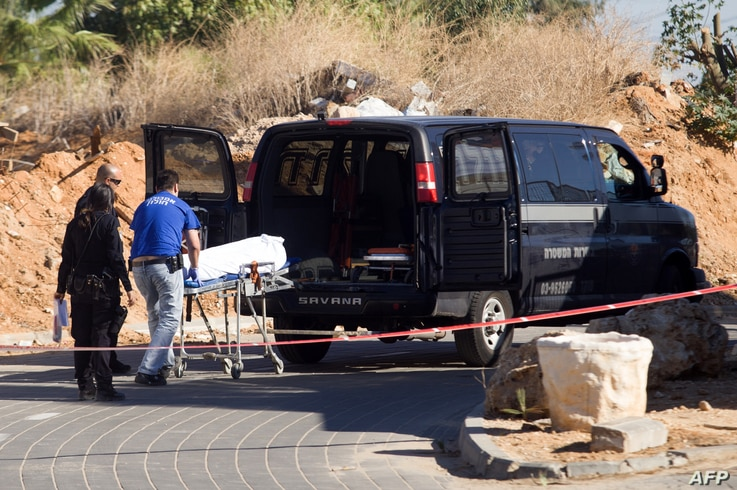 The body of a Palestinian is evacuated after he was killed during a raid by Israeli border police in a cemetery aimed at netting illegal immigrants in Petah Tikva, Nov. 30, 2013.