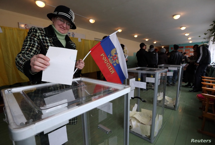 A woman holds a Russian flag as she casts her ballot during the referendum on the status of Ukraine's Crimea region at a polling station in Bakhchisaray March 16, 2014.