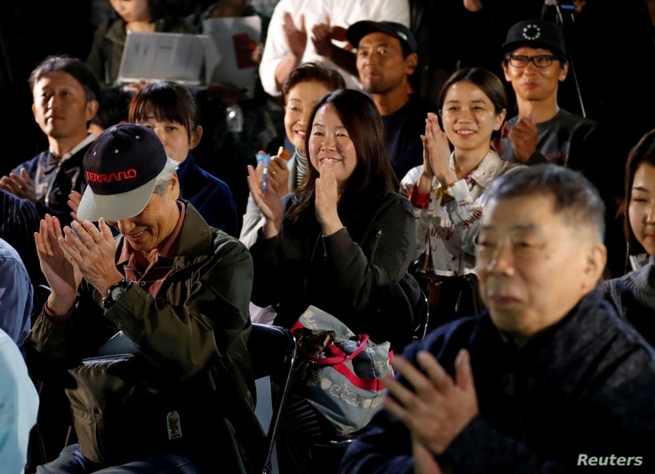 Fans of the Japanese writer Haruki Murakami celebrate after they heard that Japanese-born Kazuo Ishiguro won the Nobel Prize for Literature while they gather in a shrine with the hope of celebrating Murakami's winning in the prize in Tokyo, Japan, Oc...