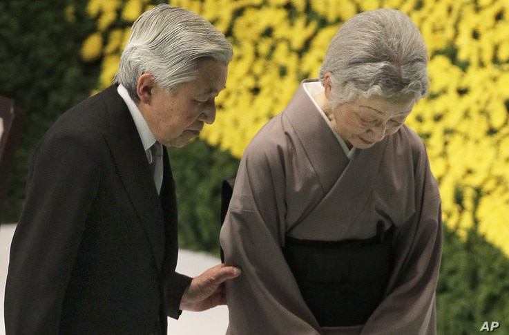 Japan's Emperor Akihito, left, escorts Empress Michiko after offering prayers for the war dead during a memorial service at Budokan Martial Arts Hall in Tokyo, Aug. 15, 2012.