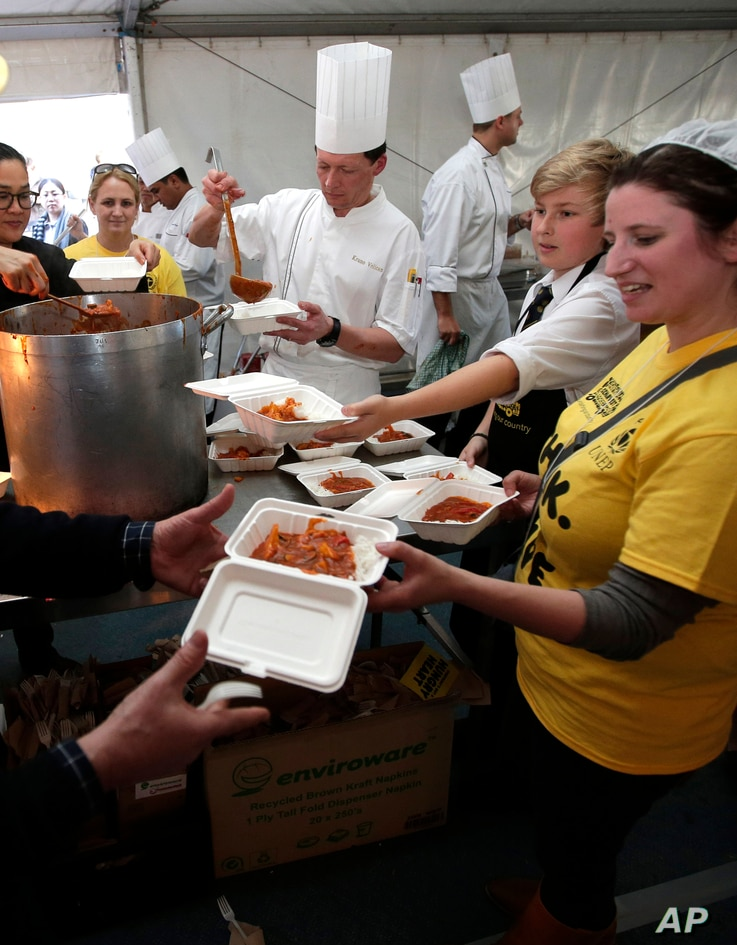 FILE - Volunteers hand out free meals made from rescued ingredients organized by the charity organization OzHarvest in Sydney's central business district, July 29, 2013. The organizers goal is to feed 5,000 people over a lunch period in a bid to rais...