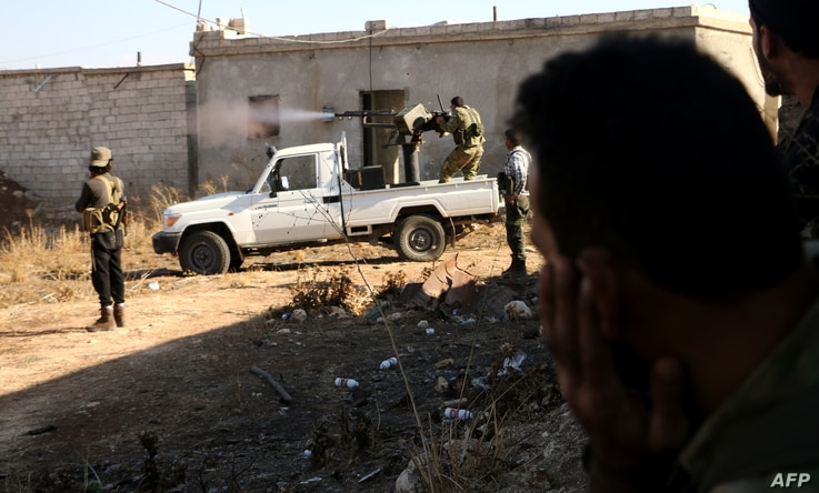 Fighters from the Free Syrian Army fire a machine gun mounted on a vehicle deployed during fighting against Islamic State group jihadists on the outskirts of the northern Syrian town of Dabiq, Oct. 15, 2016.