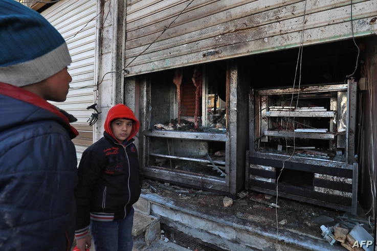 Syrian boys look at the destroyed grills outside a shuttered restaurant that was the site of a suicide attack targeting U.S.-led coalition forces in Manbij, Syria, the previous day, on Jan. 17, 2019. Islamic State claimed responsibility for the attac...