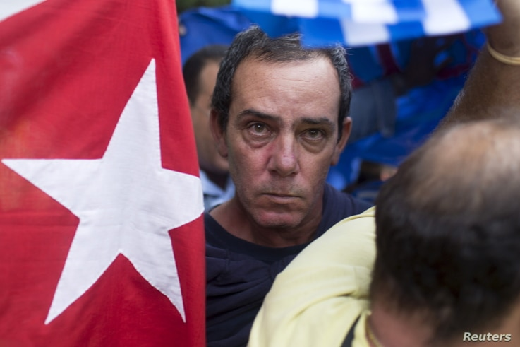 A supporter of the Ladies in White dissident group looks on as he is detained by Cuban security personnel during a protest on International Human Rights Day, Havana, December 10, 2015.