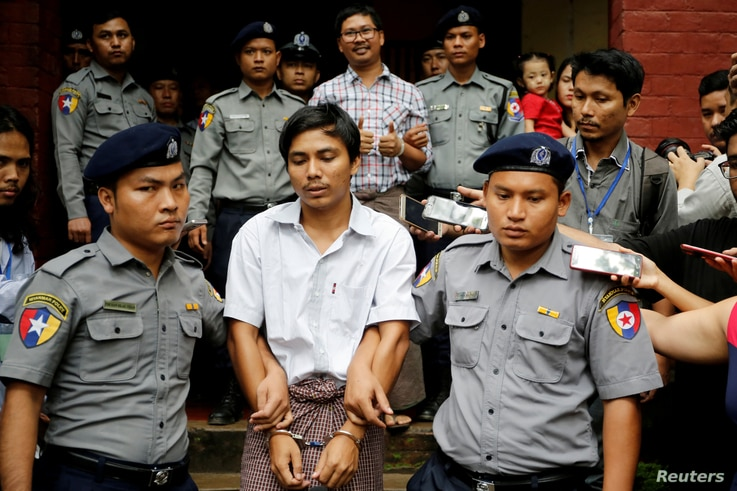 FILE PHOTO: Detained Reuters journalist Kyaw Soe Oo and Wa Lone are escorted by police as they leave after a court hearing in Yangon, Myanmar, August 20, 2018. REUTERS/Ann Wang/File Photo - RC13AD58E630