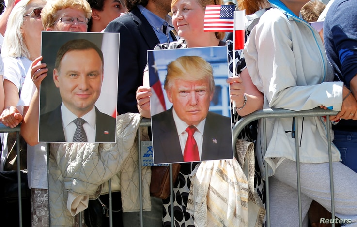 People hold images of Polish President Andrzej Duda and U.S. President Donald Trump during Trump's public speech at Krasinski Square, in Warsaw, Poland, July 6, 2017.