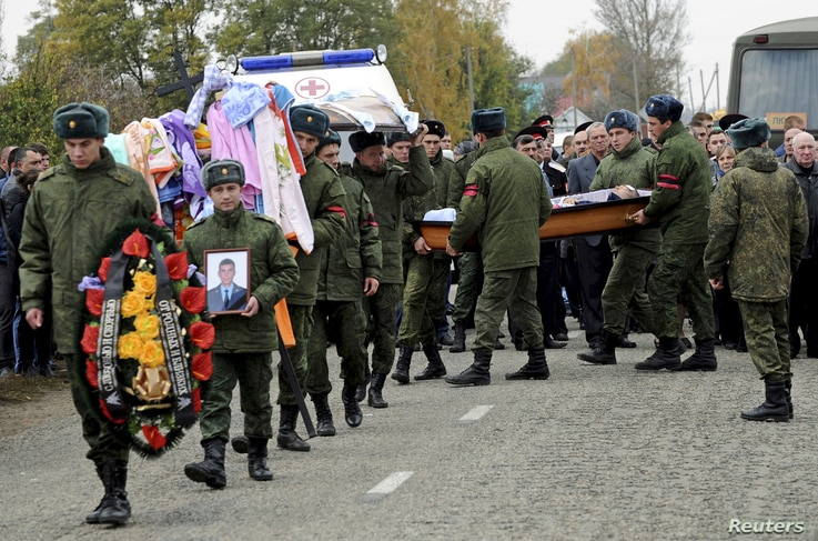 Russian servicemen carry the coffin of Vadim Kostenko, one of the Russian air force's support staff in Syria, during his funeral in the village of Grechnaya Balka, north-west of Krasnodar, Russia, Oct. 28, 2015.
