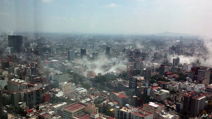 In this photo provided by Francisco Caballero Gout, shot through a window of the iconic Torre Latina, dust rises over down town Mexico City during a 7.1 earthquake, Sept. 19, 2017.