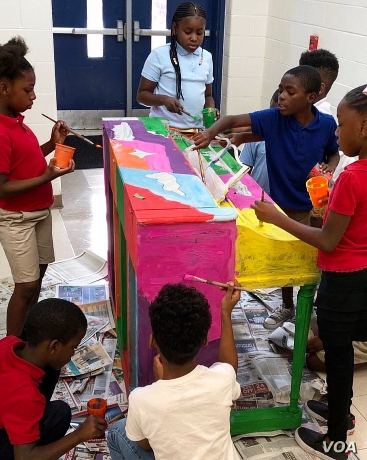 Children paint one of the pianos that will be placed in Atlanta, Georgia, during the second annual festival of Pianos for Peace festival, which runs through Sept. 22. The pianos will be donated to schools after the festival ends.